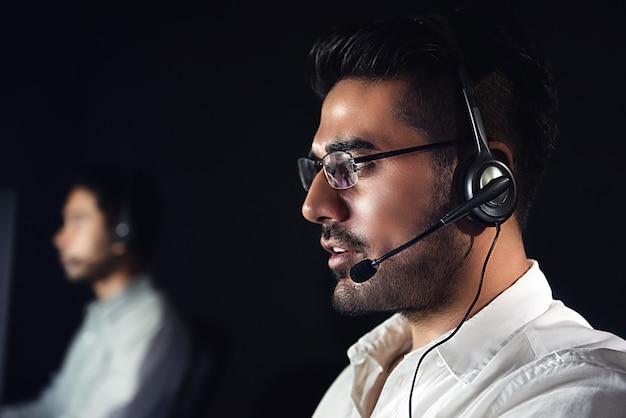 Azjatyccy męscy obsługa klienta operatorzy pracuje nocną zmianę w centrum telefonicznym