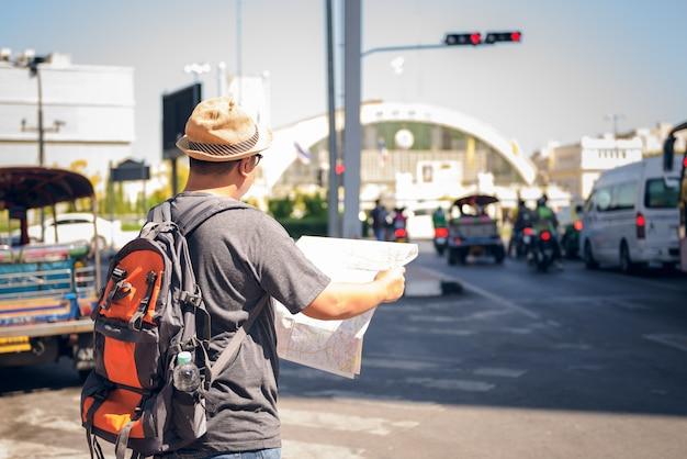 Azjatyccy męscy plecaków turyści stoi na drodze i trzyma mapę