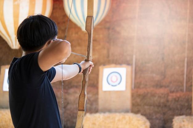 Azjatyccy mężczyzna strzelają łuczniczką skupiają się przy bramkowym obiektywnym miejsce docelowe wygrany wyzwaniem