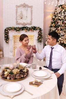 Azjatyccy mężczyźni i kobiety świętują boże narodzenie, pijąc wino przy stole jadalnym przy drzewie i kominku