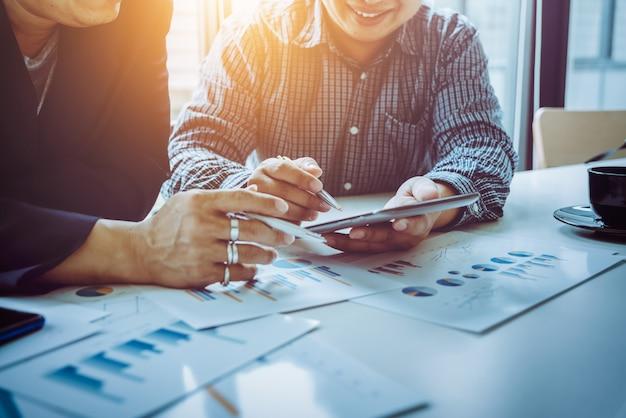 Azjatyccy mężczyźni i koledzy w średnim wieku analizowanie wykresów biznesowych.