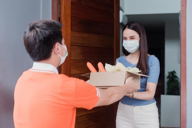 Azjatyccy mężczyźni noszą produkty dostawy w pomarańczowych koszulach.