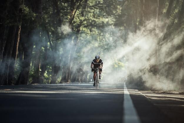 Azjatyccy mężczyźni są rowerem szosowym na rowerze rano