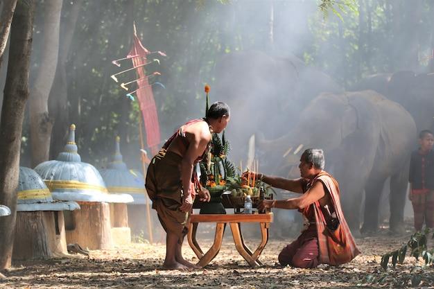 Azjatyccy mężczyźni w rodzimych tradycyjnych strojach siedząc przy ceremonii zbiorów