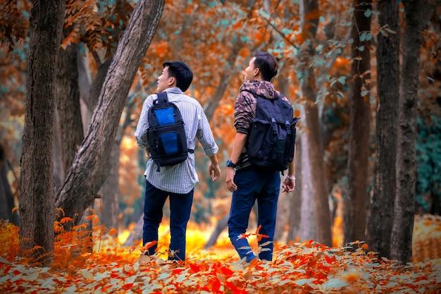 Azjatyccy mężczyźni z plecak cyny jesień las