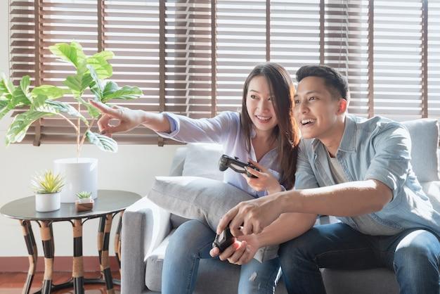 Azjatyccy miłośnicy par cieszą się i grają w gry konsolowe na wakacjach, aby spędzić więcej czasu na szczęście w domu