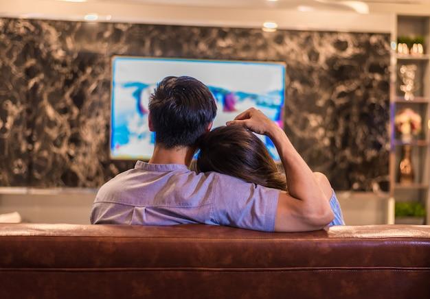 Azjatyccy młodzi kochankowie ogląda telewizję na kanapie