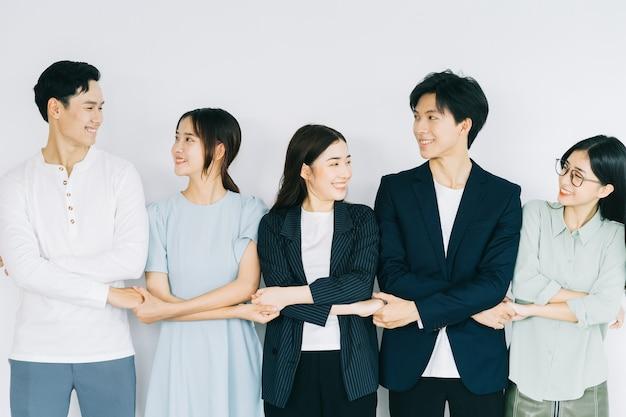 Azjatyccy młodzi ludzie biznesu trzymają się za ręce, aby okazać solidarność