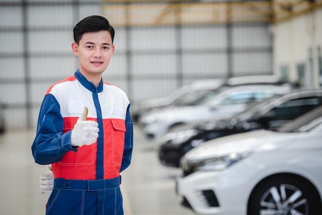 Azjatyccy motocykliści noszą kombinezony wyścigowe w warsztatach samochodowych i centrach napraw samochodowych.