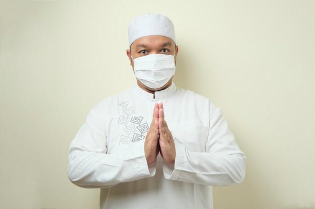Azjatyccy muzułmanie noszący maskę z gestami pozdrowienia dla gości