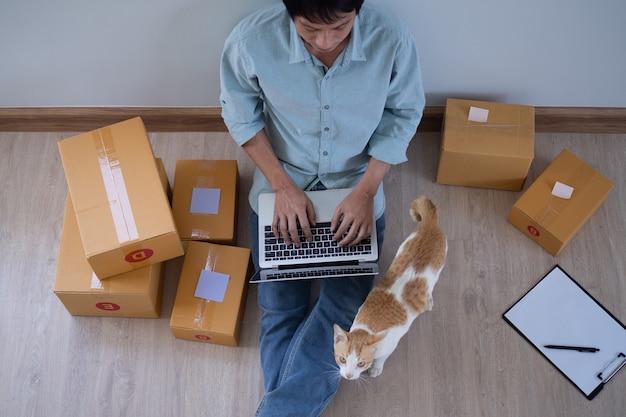 Azjatyccy przedsiębiorcy płci męskiej i sprzedaż internetowa. mężczyzna jest samozatrudniony, pracuje w domu z właścicielem małej firmy. dostawa opakowań i marketing online dla mśp