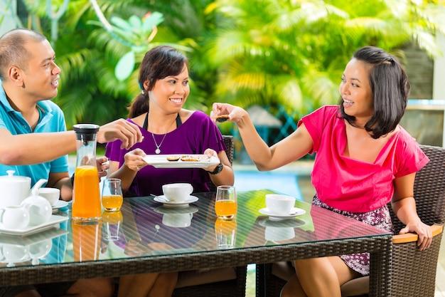 Azjatyccy przyjaciele ma kawę na domowym ganeczku