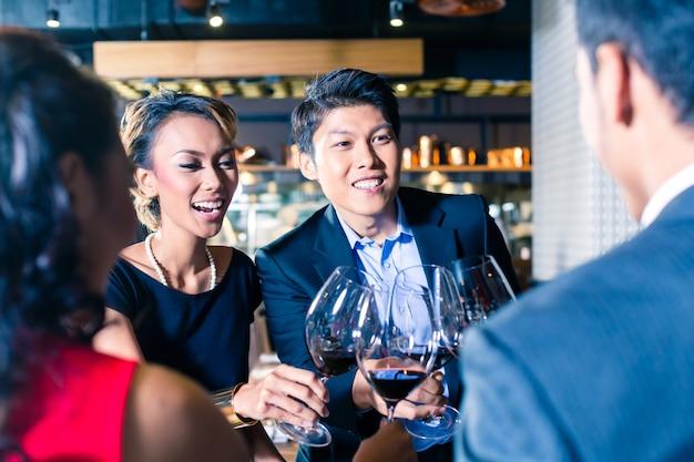 Azjatyccy przyjaciele opiekania z czerwonym winem w barze