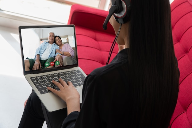 Azjatyccy rodzice biorą udział w wideokonferencji z córką podczas wakacji