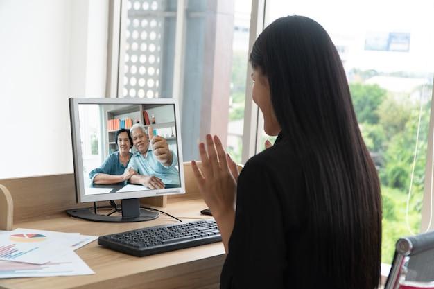 Azjatyccy rodzice biorą udział w wideokonferencji z córką podczas wakacji.