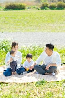 Azjatyccy rodzice i dzieci bawią się na pikniku na zielonym terenie