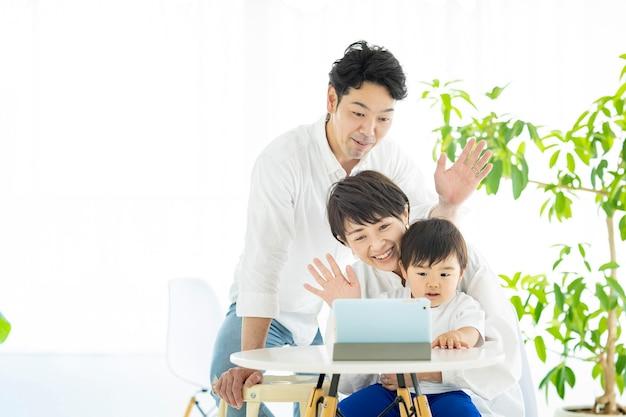 Azjatyccy rodzice i dziecko komunikują się online za pomocą tabletu