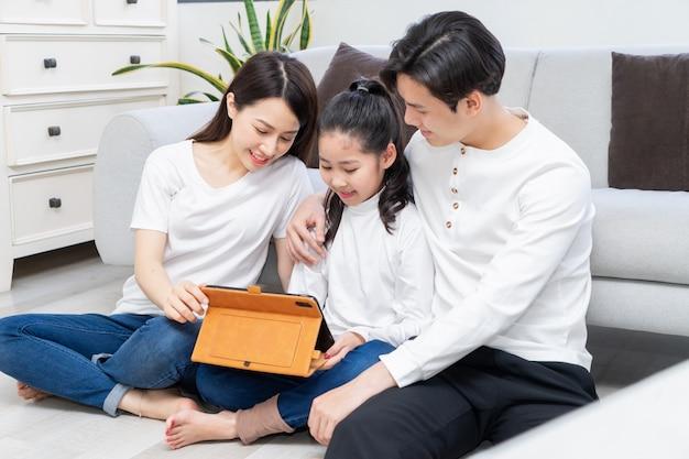 Azjatyccy rodzice pomagają córce korzystać z tabletu
