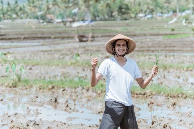 Azjatyccy rolnicy stoją w kapeluszu, trzymając rośliny ryżu do sadzenia na polach