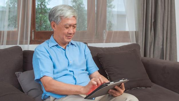 Azjatyccy starsi mężczyzna używa pastylkę w domu. azjatycka starsza chińska męska rewizi informacja o dlaczego dobre zdrowie na internecie podczas gdy kłamający na kanapie w żywym pokoju pojęciu w domu.