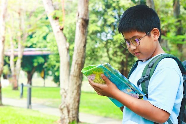 Azjatyccy studenci noszący plecak podróżny, trzymający mapę do podróży, aby się uczyć