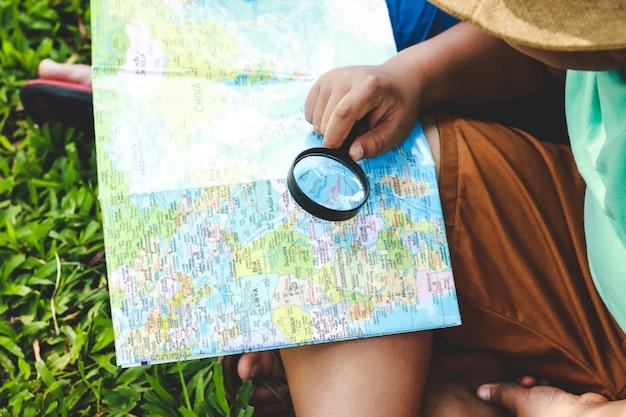 Azjatyccy studenci noszący plecak podróżny, w kapeluszu, trzymający mapę, aby się uczyć
