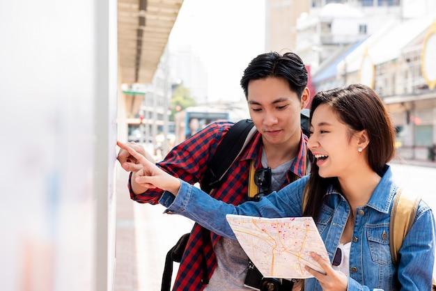 Azjatyccy turyści patrzeje dla tavel informaci w bangkok mieście tajlandia