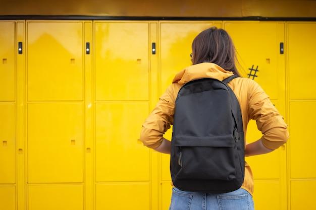 Azjatyccy turyści stoją przed automatyczną szafką na bagaż.