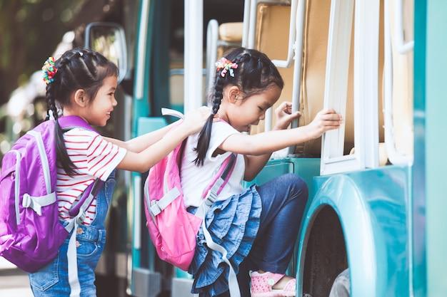 Azjatyccy uczni dzieciaki z plecaka mienia ręką i iść szkoła z autobusem szkolnym wpólnie