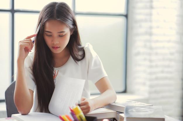 Azjatyccy uczniowie czytają książkę. w bibliotece uniwersyteckiej