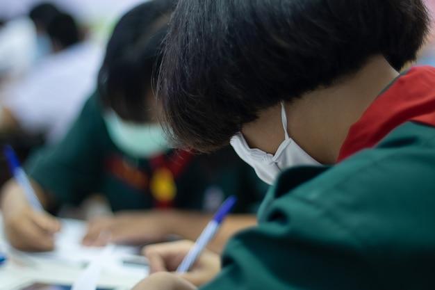 Azjatyccy uczniowie w mundurach noszą maskę, zamierzając uczyć się w klasie.