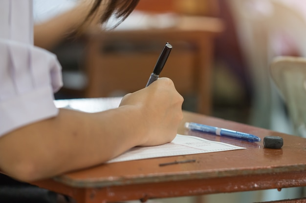 Azjatyccy uczniowie wręczają egzaminy, pisze egzaminacyjnym mieniu ołówek na optycznym forma tescie
