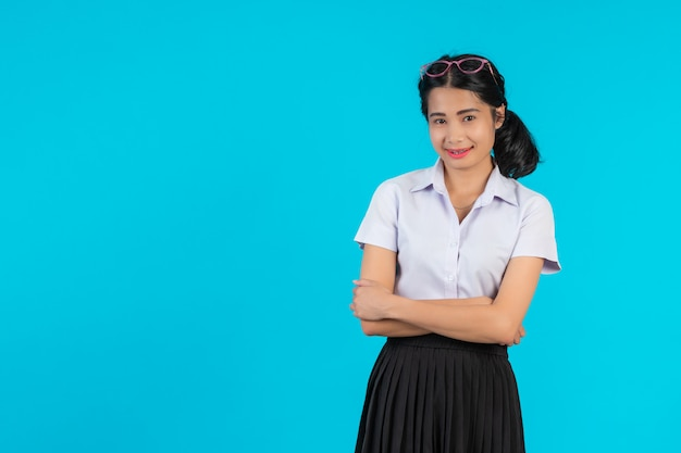 Azjatyccy żeńscy ucznie pozuje w różnorodnych pozycjach na błękicie.