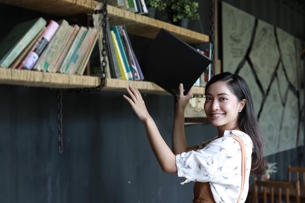 Azjatyccy żeńscy ucznie trzyma dla sekci na książkowej półce
