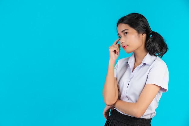 Azjatyccy żeńscy ucznie wykonuje różnorodnych gesty na błękicie.
