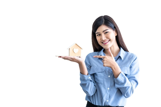 Azjatycka atrakcyjna biznesowa kobieta pokazuje i trzyma model domu na białym odosobnionym tle
