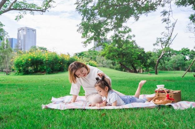 Azjatycka babcia i wnuczka kłaść na zielonego szkła polu plenerowym, rodzinny cieszy się piknik wpólnie w letnim dniu