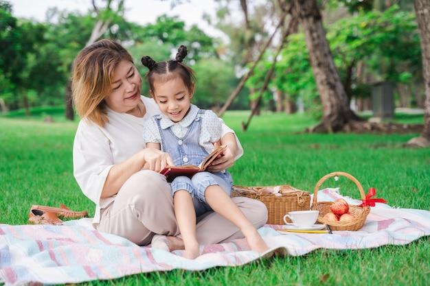 Azjatycka babcia i wnuczka siedzi na zielonym szkle pole plenerowym, rodzinny cieszy się piknik wpólnie w letnim dniu