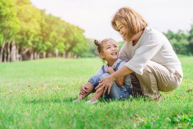 Azjatycka babcia i wnuki ma szczęśliwego czas w parku wpólnie