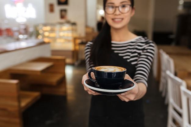 Azjatycka barmanka przedłuża filiżankę kawy