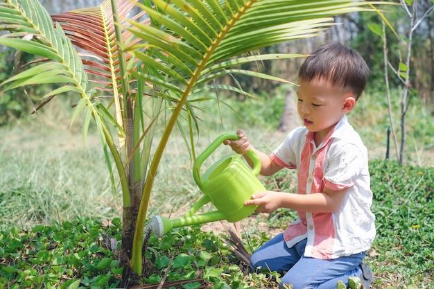 Azjatycka berbeć chłopiec nawadnia młodego drzewa z podlewanie puszką