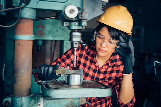 Azjatycka beuatiful kobieta pracuje z maszyną w fabrycznym inżyniera i pracującej kobiety dniu kobiety lub pojęciu