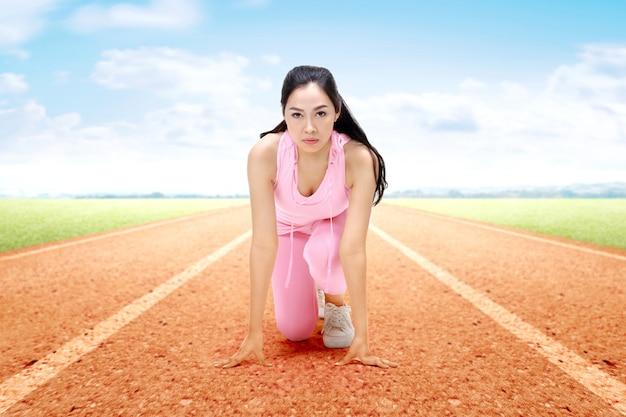 Azjatycka biegacz kobieta przygotowywająca biegać na bieg śladzie