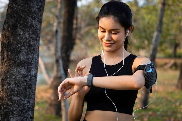 Azjatycka biegaczka używa inteligentnego zegarka do monitorowania swoich wyników. sportowiec ustawia aplikację fitness na smartwatchu przed uruchomieniem sesji.