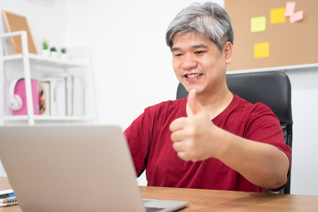 Azjatycka biznesmen wideokonferencja dzwoni na laptopie do edukacji online w domu.