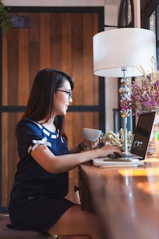 Azjatycka biznesowa kobieta pracuje z laptopem robi notatce w sklep z kawą jak tło.
