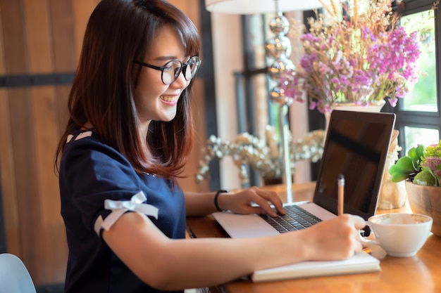 Azjatycka biznesowa kobieta pracuje z robi notatce z laptopem i notatnikiem
