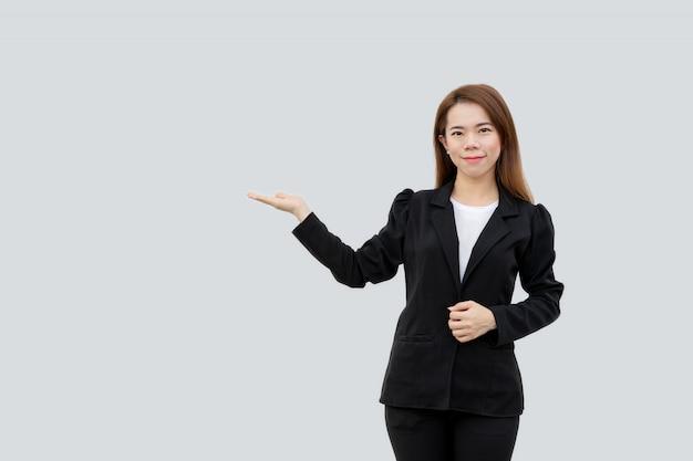 Azjatycka biznesowa kobieta przedstawia rękę z długimi włosami w czarnym kostiumu odizolowywającym na białym kolorze