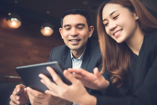Azjatycka biznesowa para cieszy się używać pastylka komputerowego surfuje internet w kawiarni