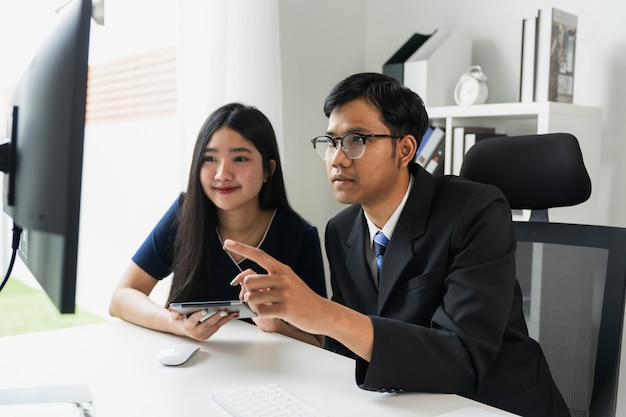 Azjatycka biznesowa praca zespołowa używa komputer z pastylką i zgłasza wykresy.